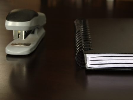 Notepad sitting on a desk with a stapler photo
