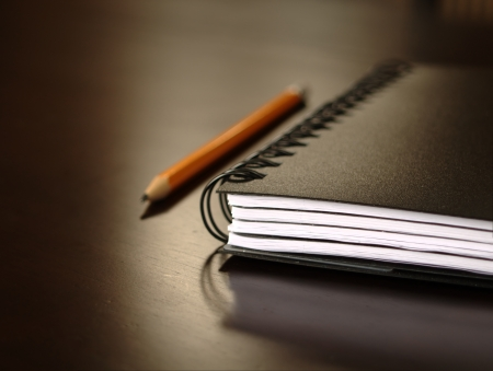 Notepad sitting on a desk with a pencil photo