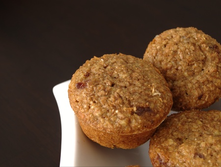 Cranberry Bran Muffins sitting on a white plate with a dark background Stok Fotoğraf - 18942351