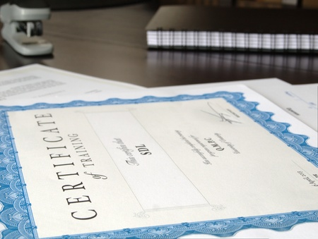 financial official: Certificate and Business Documents laid out on a dark table