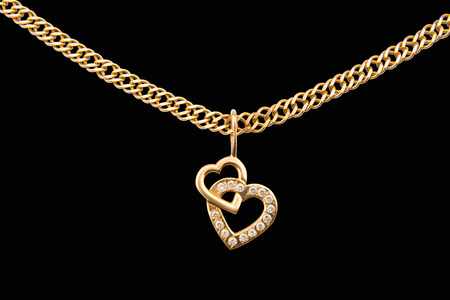 Gold chain and pendant in the shape of heart on a white background