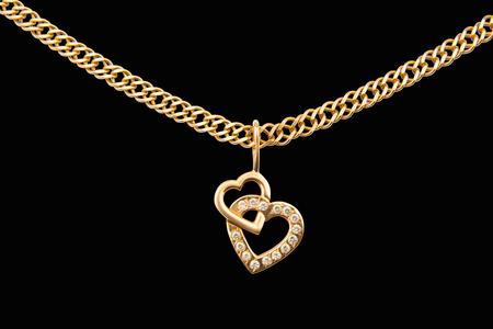 Złoty łańcuszek i zawieszka w kształcie serca na białym tle Zdjęcie Seryjne