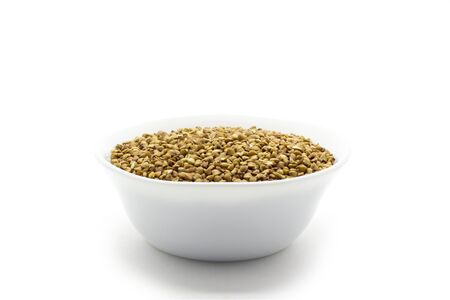 Dry buckwheat in white ceramic bowl isolated on white