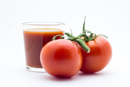 Glass with tomato juice and fresh tomatoes on white background