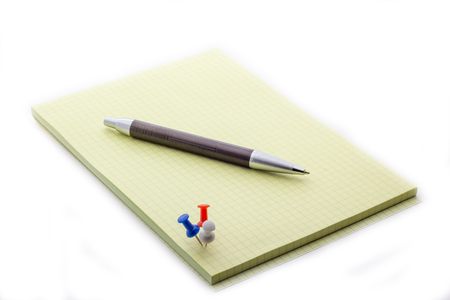The pen lies on a notepad, next to the button