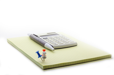 The calculator lies on a notepad, next to the pen Banco de Imagens