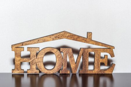 The word home is made of wood on a dark table 写真素材