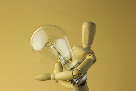wooden person holds electric bulb in hand Stock Photo