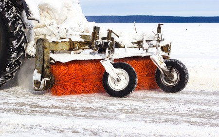 Tractor cleans road from snow after blizzard. Bad winter weather conditions and transport service concept.