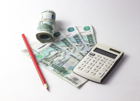 Money with a calculator lying on a white background