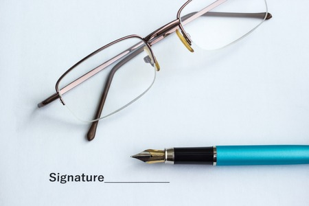 Document for signing beside glasses and pen, close-up