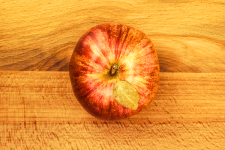 Fruit of a red apple with leaves on a wooden background
