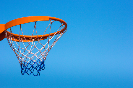 Basketball hoop against the blue sky, close-up