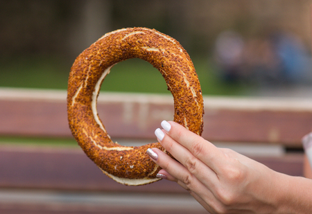 Girl holding a Turkish bagel (simit) in her hand, close-up