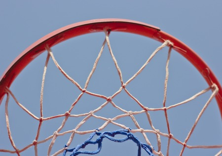 Close-up basketball hoop rim, up ward view a hoop under blue sky