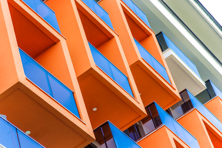 Abstract fragment of modern architecture, facade and orange balconies, close-up