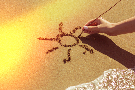 A woman's hand draws the sun on the sand by the sea, the glow effect 版權商用圖片