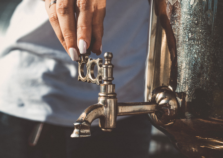 The girls hand turns the tap of the old samovar Stock Photo