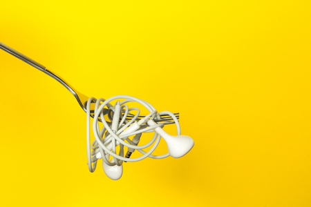 Fork and headphones on a yellow background