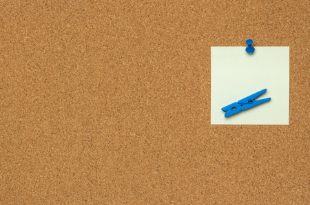 One colorful notes with blue pushpins and clothespins isolated on a cork background