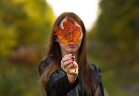 Young beautiful woman in autumn park holds a maple leaf