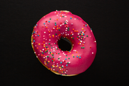 Donut pink with sprinkles isolated on black background, close-up