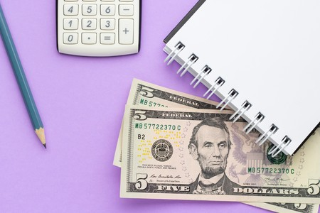 Calculator, notebook with american money and a pencil on a lilac background