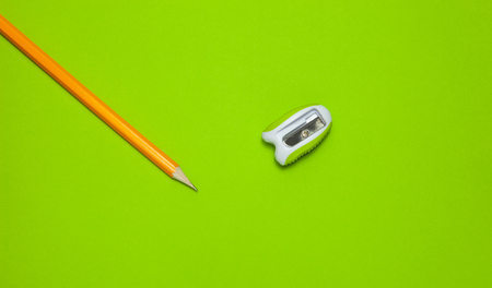 Pencil and sharpener on a green background, top view