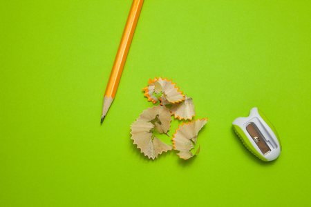 Sharpened pencil and sharpener on green background, top view