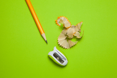 Sharpened pencil and sharpener on green background Imagens