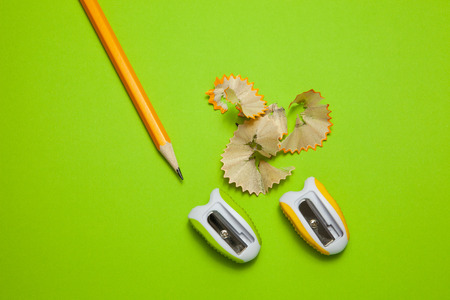Sharpeners and pencil on green background, close-up