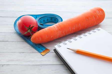 Measuring tape with a notepad, juicy tomato and carrot, the concept of healthy eating and weight loss Stockfoto