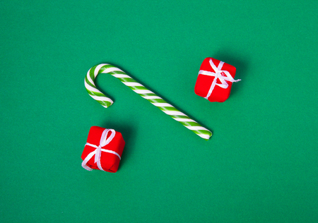 Christmas candy and gift boxes on green background, top view