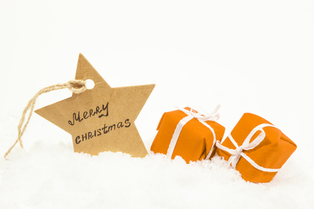 Orange gifts on white snow and a star with the inscription Merry Christmas Standard-Bild