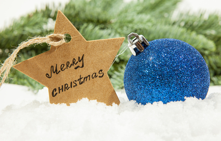 Christmas ball in blue on white snow and a star with the inscription Merry Christmas, in the background fir branches, New Year's theme Stock Photo