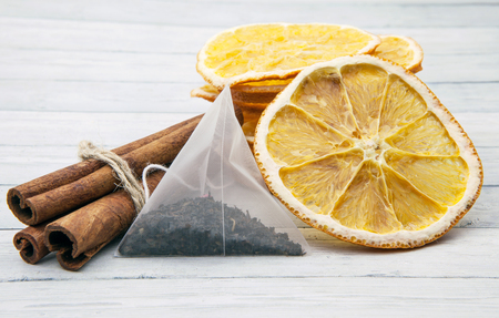 Orange slices with cinnamon and tea bag on a light wooden background, tea drinking concept