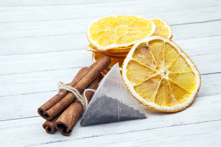 Slices of orange with cinnamon and tea bag on a light wooden background, enjoying the spices