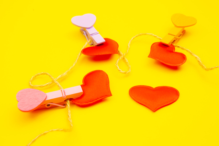 Hearts with clothespins lie on a yellow background tied with a rope.