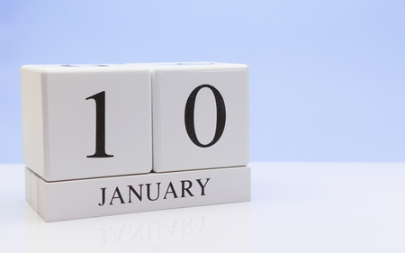 January 10st. Day 10 of month, daily calendar on white table with reflection, with light blue background. Winter time, empty space for text