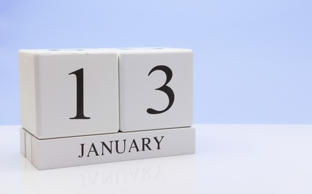 January 13st. Day 13 of month, daily calendar on white table with reflection, with light blue background. Winter time, empty space for text