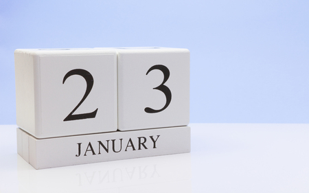 January 23st. Day 23 of month, daily calendar on white table with reflection, with light blue background. Winter time, empty space for text