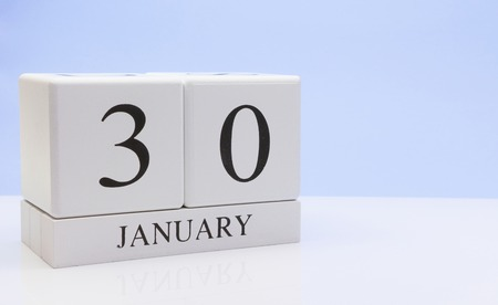 January 30st. Day 30 of month, daily calendar on white table with reflection, with light blue background. Winter time, empty space for text