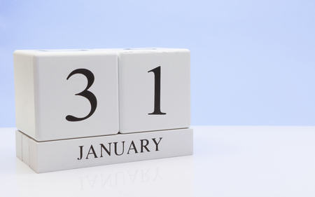 January 31st. Day 31 of month, daily calendar on white table with reflection, with light blue background. Winter time, empty space for text