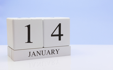 January 14st. Day 14 of month, daily calendar on white table with reflection, with light blue background. Winter time, empty space for text
