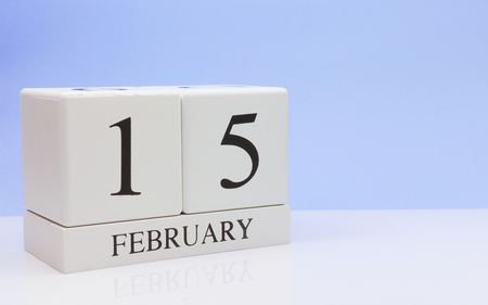 February 15st. Day 15 of month, daily calendar on white table with reflection, with light blue background. Winter time, empty space for text
