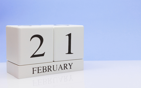 February 21st. Day 21 of month, daily calendar on white table with reflection, with light blue background. Winter time, empty space for text