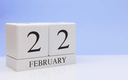 February 22st. Day 22 of month, daily calendar on white table with reflection, with light blue background. Winter time, empty space for text