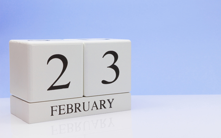 February 23st. Day 23 of month, daily calendar on white table with reflection, with light blue background. Winter time, empty space for text