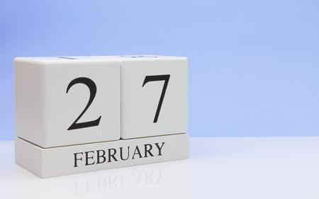 February 27st. Day 27 of month, daily calendar on white table with reflection, with light blue background. Winter time, empty space for text Stock Photo