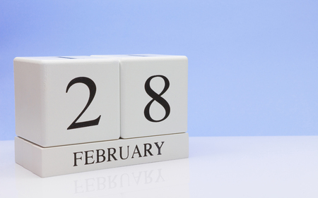 February 28st. Day 28 of month, daily calendar on white table with reflection, with light blue background. Winter time, empty space for text Banco de Imagens